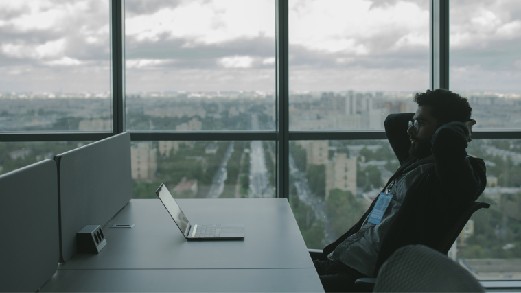 man at a desk leaning back with hands on head comfortably looking at laptop while office window overlooks city