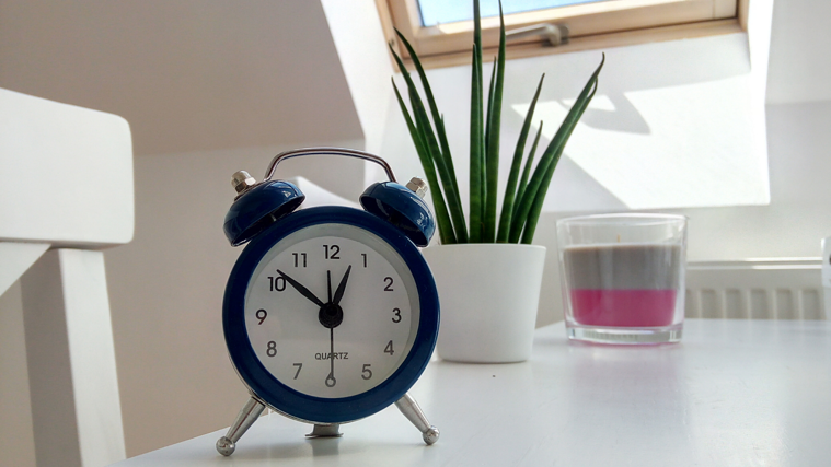 Analog clock on sleek table with plant and candle