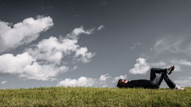 Person wearing sunglasses laying on grass looking up at sky with wispy clouds