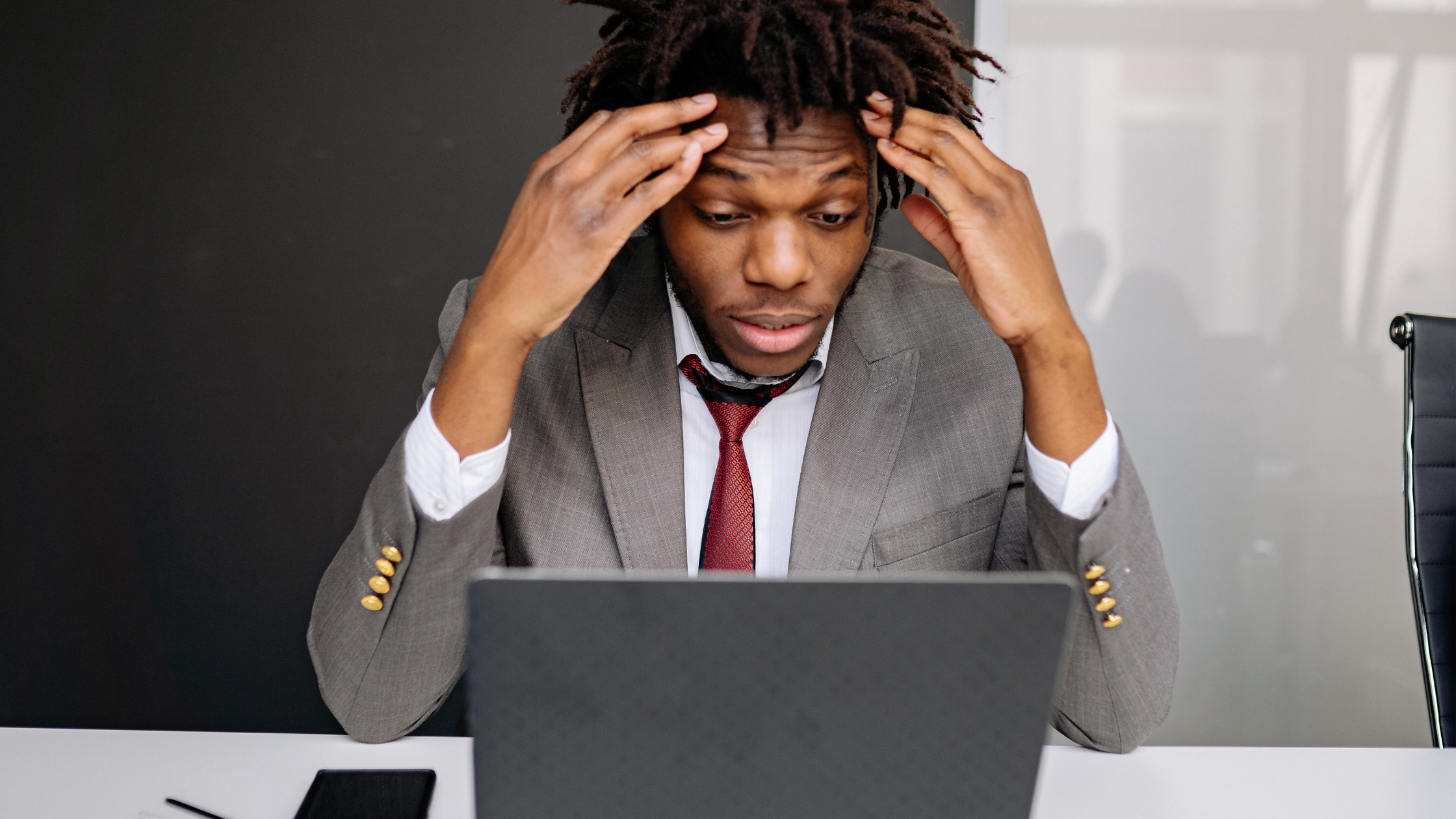 Man with hands on head staring at laptop frustrated