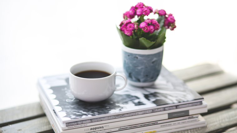 stack of magazines with a cup of coffee and pink flowers on top