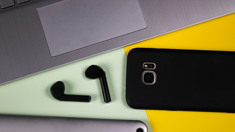 Computer, phone, device and ear buds on a green and yellow surface