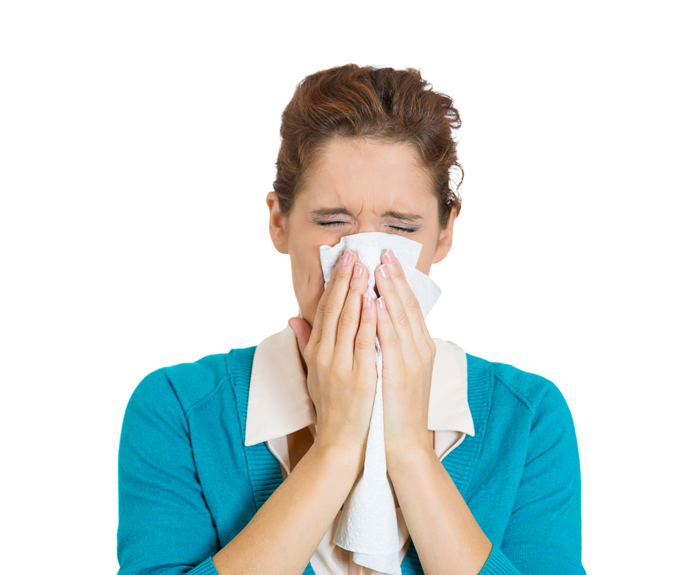 person blowing nose into tissue