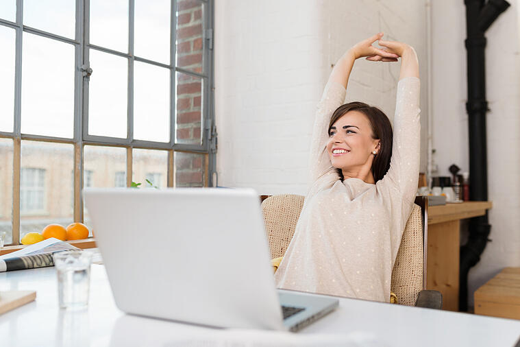 woman stretching at laptop computer