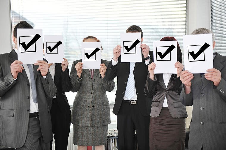 business people holding an image of checked off boxes