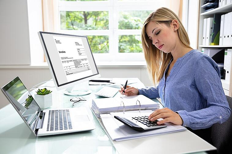 business woman at desk using a calculator